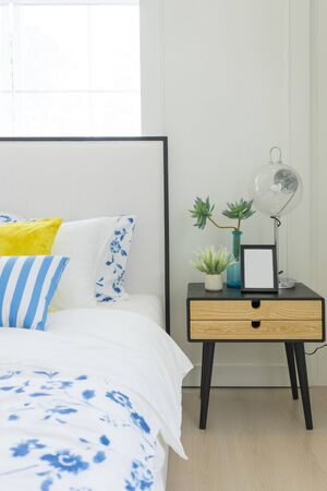 Bright bedroom interior with striped pillow on bed and bedside table lamp with picture frame on it.