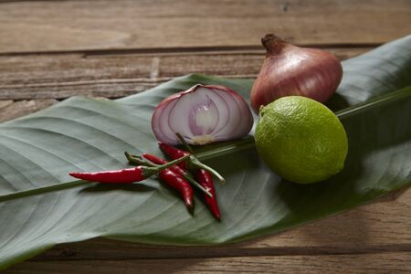 Ingredients set for Thai spicy soup (Tom-yum) include lemon, red chili, red onion lemongrass and green lime on wood table. Stock Photo