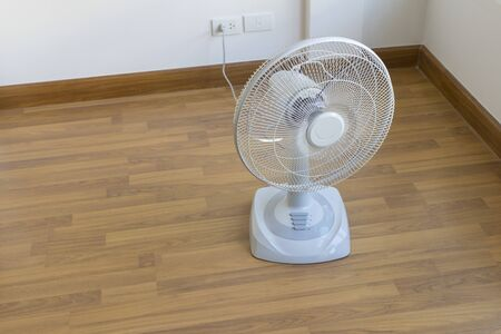 Table electric fan sit on the wooden floor Banco de Imagens