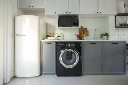 Interior of modern kitchen with washing machine. Laundry day