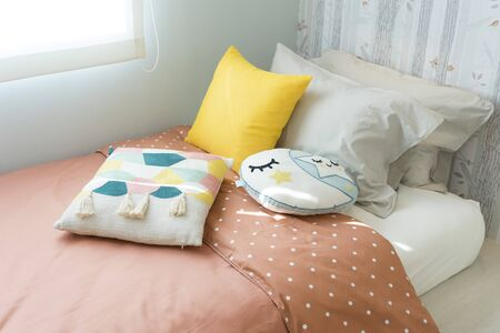 Kid bedroom with cute pillows and yellow table lamp on side table.