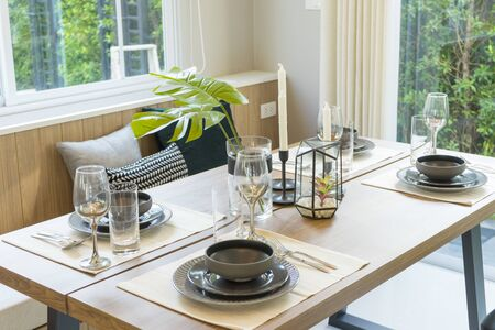 Modern dinning room interior with grey plate on wood table at home.