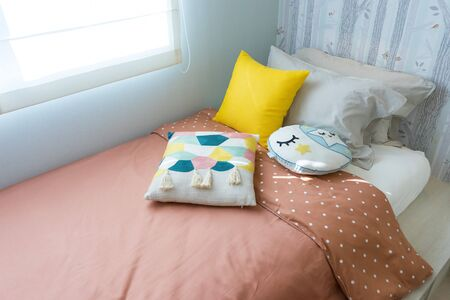 kid bedroom with cute pillows and yellow table lamp on side table. Stockfoto
