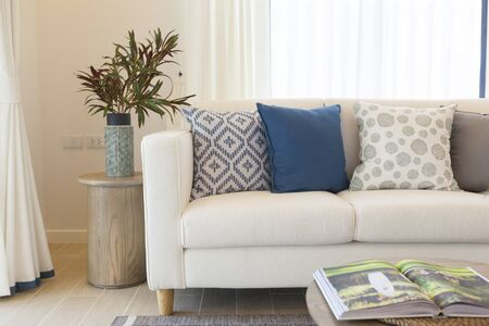 White sofa with many blue pillows in cozy living room Stockfoto