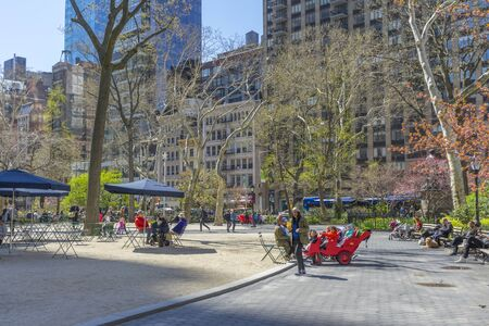 People enjoy the weather on a spring day at Bryant Park in New York City,USA