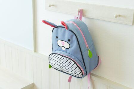 blue school rucksack hanging on the wall in kid bedroom.