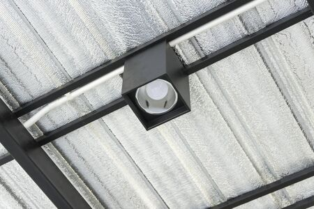 Close up of LED bulb in the lamp mounted under the roof.