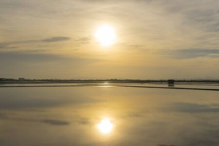 Salt farm in the morning with sunrise sky and clouds. Landscape of sea salt field in Thailand.