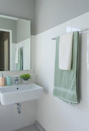 Gros plan sur une serviette verte suspendue dans une salle de bains moderne