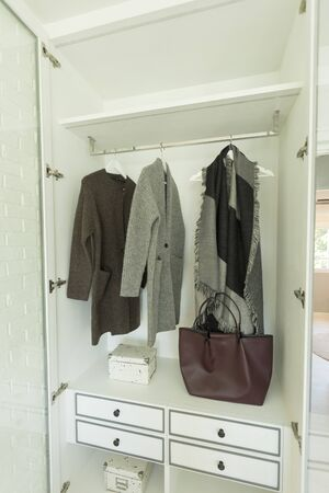 Stylish clothes and home stuff in large wardrobe closet.