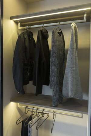 Stylish clothes and home stuff in large wardrobe closet. Zdjęcie Seryjne