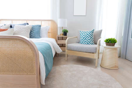 Cozy blue bedroom with modern interior, ethnic decor, comfortable bed, lamp over bedside table.