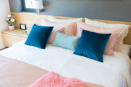 elegant bedroom interior with comfortable bed with pastel, blue and pink bedding