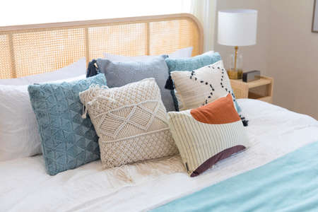 close up of new bed comfort with decorative pillows ,headboard and side table lamp. Banque d'images