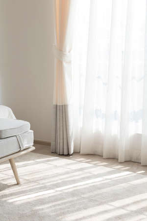 bright sunlight shines on white curtains through window of cozy home bedroom.