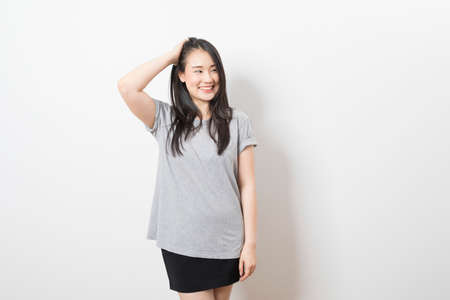 Portrait of happy young asian woman wearing grey shirt smiling at camera while standing over white background. Stockfoto