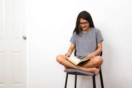 Asian college student sitting on a chair reading a book in her room.