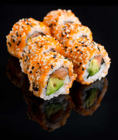 Group of sushi rolls on black reflective surface
