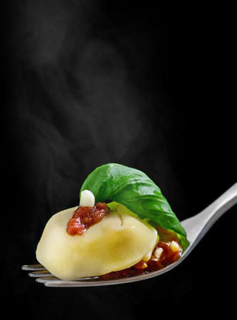 Tortellini on fork with sauce and basil Stock Photo
