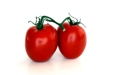 attached: Two fresh organic tomatoes with stems attached