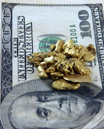 Gold nuggets palced on top of a hundred dollar bill Standard-Bild