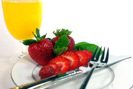 Sliced strawberries and orange juice on a white background