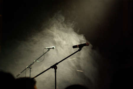 Two microphones standing in a cloud of smoke waiting for the band to arrive and start playing.