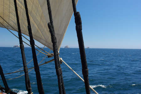 Three of the Farallon Islands viewed through the rigging of a sailing ship. Stok Fotoğraf