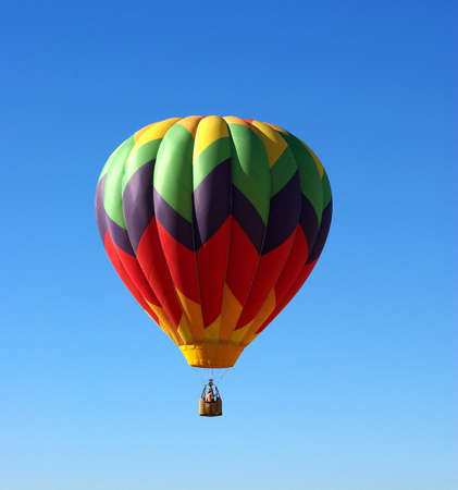 A multi colored Hot Ait Ballon rises into a clear bright sky