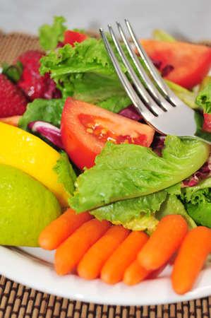 A Lite Ensalada con una mezcla de lechuga, zanahorias baby, tomate con limón y lima sobre un plato blanco y ensalada diseñador Individual.  Foto de archivo - 3545971