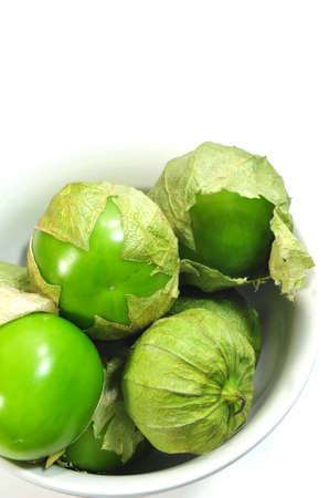 Tomatillos with husks on in a small white bowl