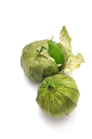 Tomatillos with husks on with one partiall pealed