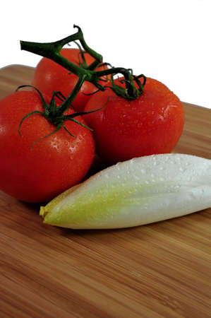 endive: Thre tomatoes and Endive on a wooden cutting board.