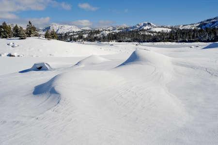 high sierra: Fresh windblown snow covering the rocks and lake in the high sierra