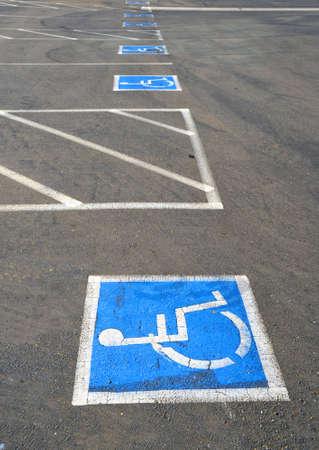 Multiple empty handicap parking spaces in an asphalt parking lot photo