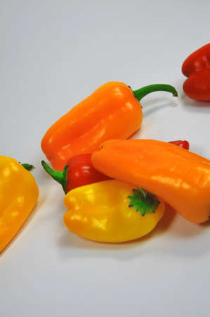 Different colored sweet peppers on a light colored background Фото со стока