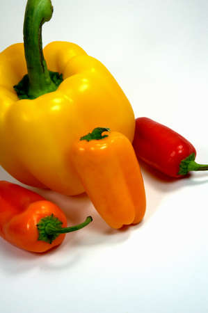 Different colored sweet and bell peppers on a light colored background Фото со стока