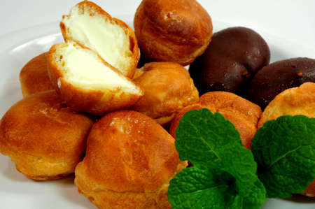 Two different kinds of cream puffs on a saucer with mint leaves photo
