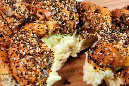 open topped: A loaf of artisan french bread topped with assorted seeds torn open to show the inside Stock Photo