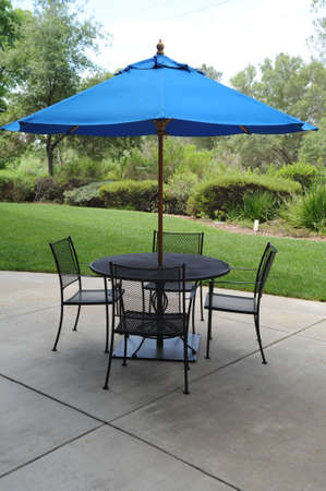 Blue umbrella, table and chairs on a patio in a graden setting