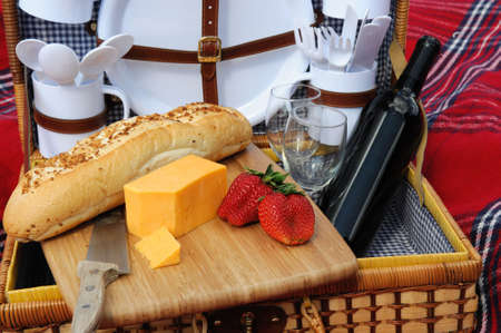 Garlic frech roll, cheddar cheese, strawberries and a bottle of red wine in a wicker picnic basket with plaens and utensils. photo