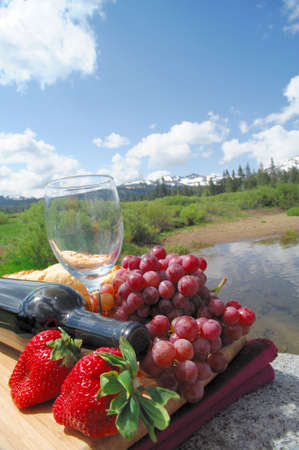 Fruit and Wine picnic in a scenic mountain setting on a bright sunny day Stock Photo