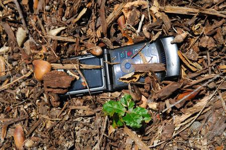 phone button: Mobiele telefoon die is verloren en gedeeltelijk bedolven onder het puin bos
