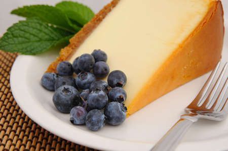 cheesecake: Seasonal blueberries with a slice of plain cheese cake with a mint leaf garnish served on a white saucer and a silver fork. Stock Photo