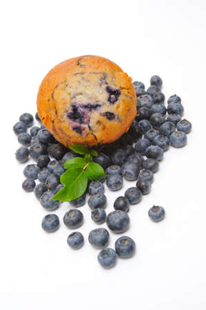 Fresh blueberries surround a single blueberry muffin on a light background