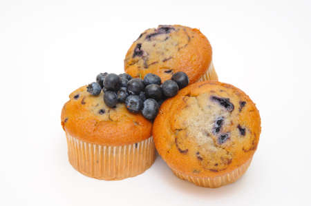muffins: Blueberry muffins with fresh blueberries on top of the cakes on a light colored background.