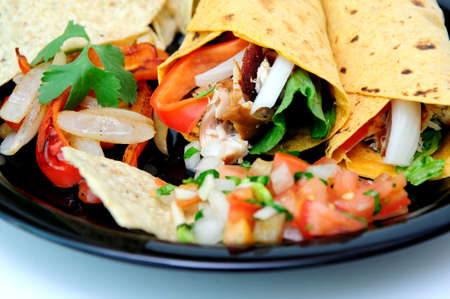 Grilled teriyaki chicken, red bell pepper, white onion, cilantro and romain lettuce are used to fill the tomato and basil wraps with grilled veggies and fresh tomato salsa and chips on the plate