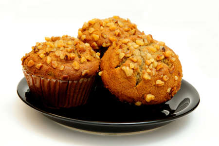 Closeup of three banana nut muffins topped with crushed walnuts on a black saucer with a light colored background.