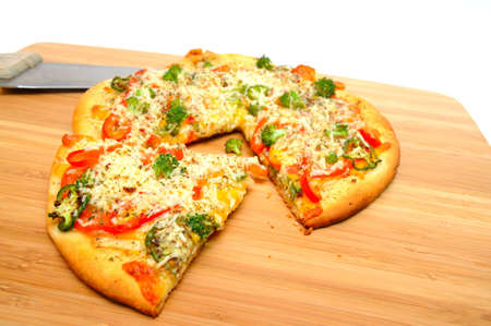 A slice of gourmet veggie pizza topped with sharp cheddar and asiago cheese, fresh tomatoes, red bell pepper, mild jalapeno chilie, broccoli and dried herbs photo