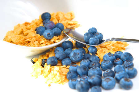 A tipped bowl of cereal and blueberries on a light background with spoon holding a few berries. Stock Photo - 5194285